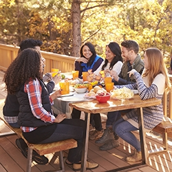 Man barbecues for friends at a table, on a deck in a forest