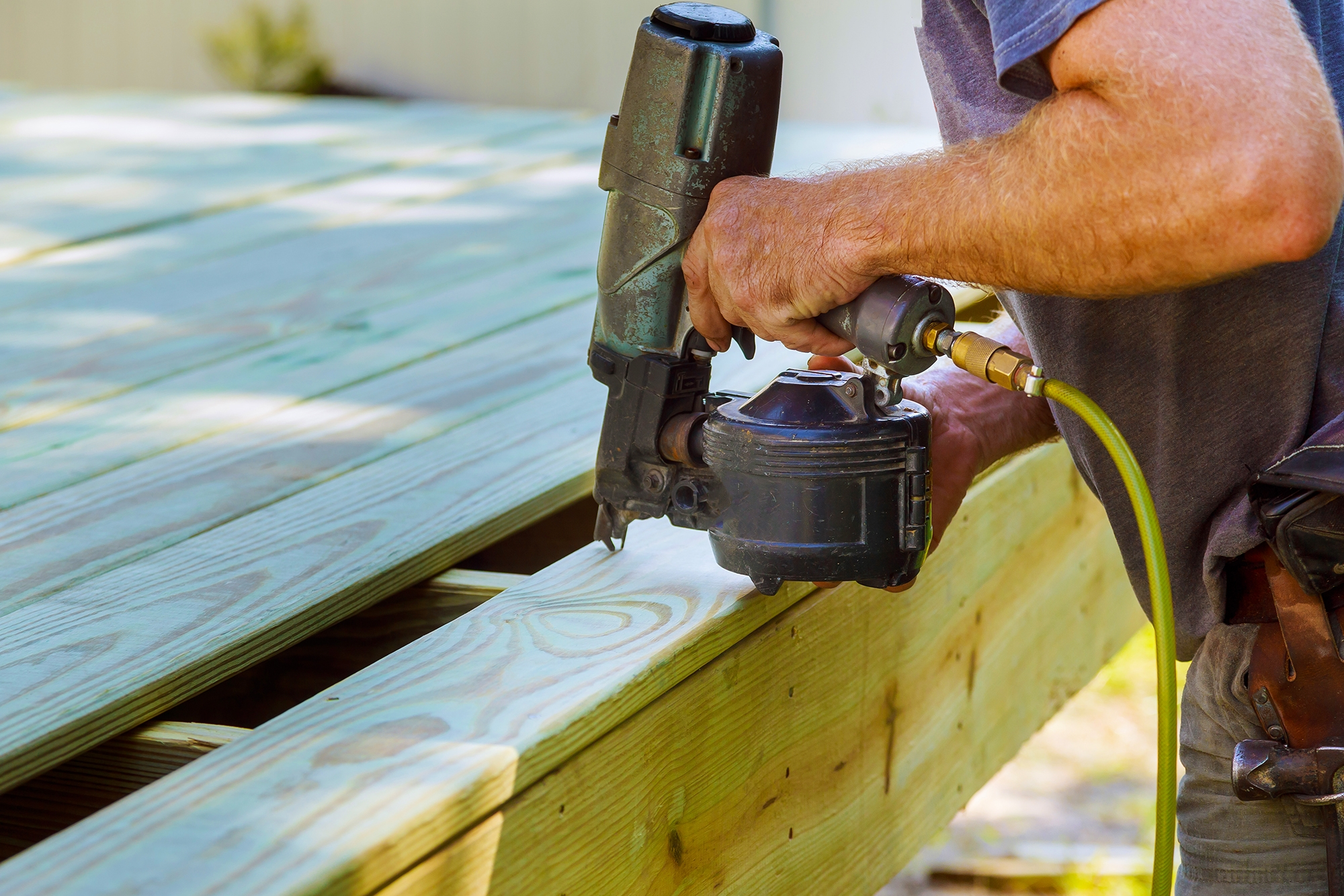 Installing Wood on deck, patio construction man using pneumatic nailer air gun
